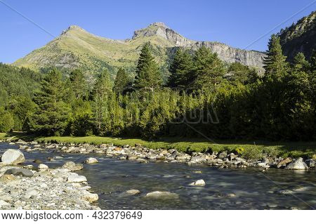 Bujaruelo Valley In The Pyrenees Mountains In Spring With The Ara River In Foreground