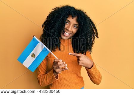 African american woman with afro hair holding argentina flag smiling happy pointing with hand and finger