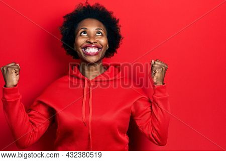Young african american woman wearing casual sweatshirt celebrating surprised and amazed for success with arms raised and open eyes. winner concept.