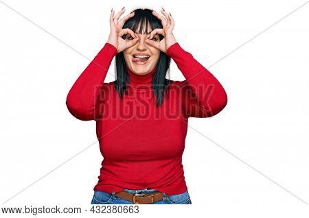 Young hispanic woman wearing casual clothes doing ok gesture like binoculars sticking tongue out, eyes looking through fingers. crazy expression.