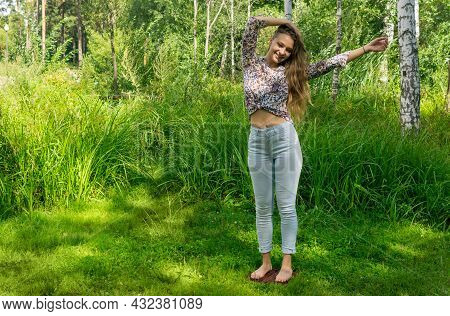 Young Woman Stands Barefoot On A Board With Nails Doing Yoga Practice Outdoors