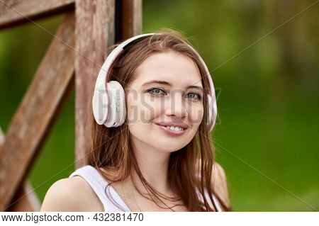 Wireless Headphones On Pleasant Young Woman In Park.