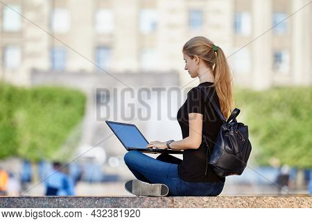 Remote Work Or E-learning Outdoors, Young Woman Uses Laptop For Online Education Or Teleworking In C