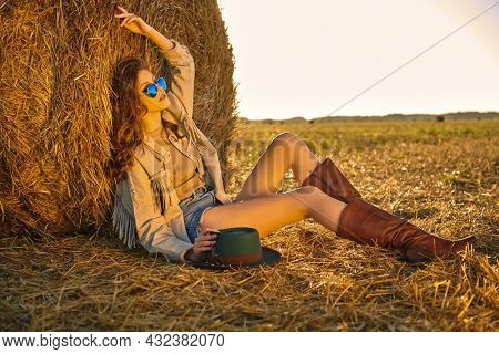 Modern hippie and bohemian style. Full length portrait of a romantic girl sitting by a haystack in a field and looking into the distance in the rays of the setting sun. Autumn fashion.
