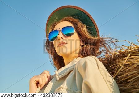 Portrait of a romantic girl in western style clothes and sunglasses looking into the distance against the blue sky. Spirit of freedom. Hippie style, fashion.