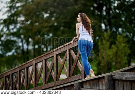 Rear View Of Woman With Beautiful Figure Standing On Wooden Landscaping Element In Public Park.