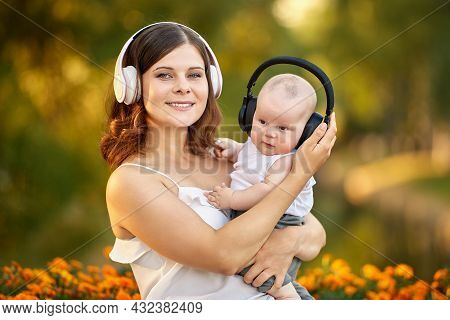 Baby And His Mother Listen To Music Through Wireless Headphones In Nature.
