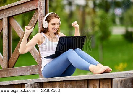 Woman In Front Of Laptop, Waiting For Good News, Sits On Wooden Fence In Public Park.