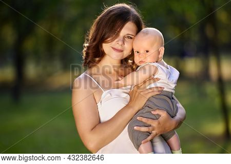 Baby In Arms Of Young Lovely Woman In Park.