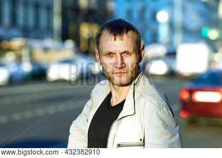 Face Of Serious Bearded Man Of About 40 On Background Of City Street.