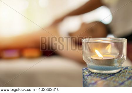 Candlelight In Cup Glass On Table Over Blurred Young Woman Lying Relax On The Bed With Masseur Massa