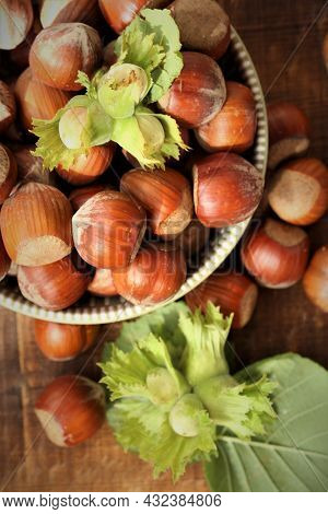 Hazelnut Close-up.nuts Abundance.nut Harvest. Ripe Nuts Plate And Green Nuts With Leaves On Wooden B