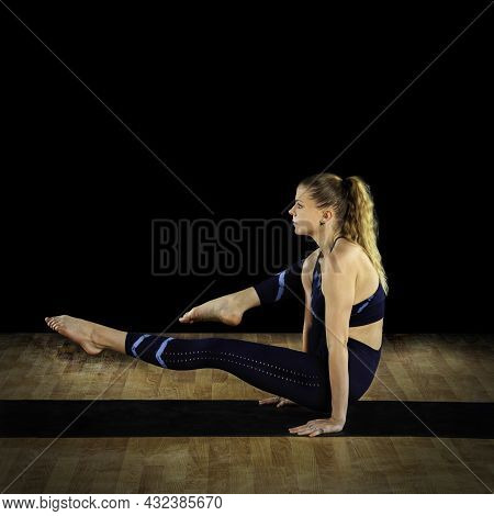 Female Instructor In A Yoga Elephant Trunk Pose Variation At A Studio.