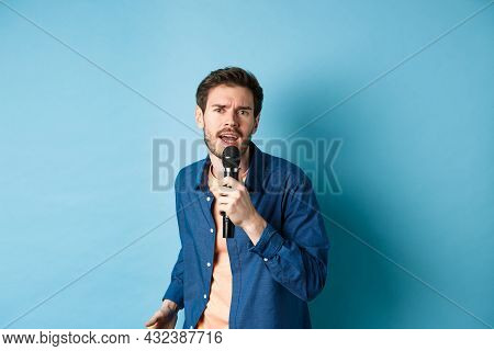 Passionate Singer Looking At Camera, Singing In Microphone, Playing Karaoke On Blue Background