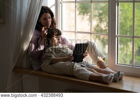 Young Mom And Kid Boy Sitting On Windowsill Look At Digital Tablet Screen Embracing. Single Mother O
