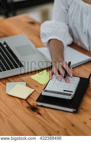 Close Up Hand Of Accountant Or Bookkeeper Using Calculator Calculating Financial Expense At Home Off