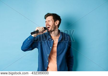 Carefree Guy Singing Karaoke With Microphone, Perform A Song, Standing On Blue Background