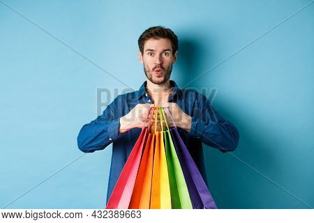 Excited Shopper Holding Packages In Paper Bags And Smiling Amused, Standing On Blue Background