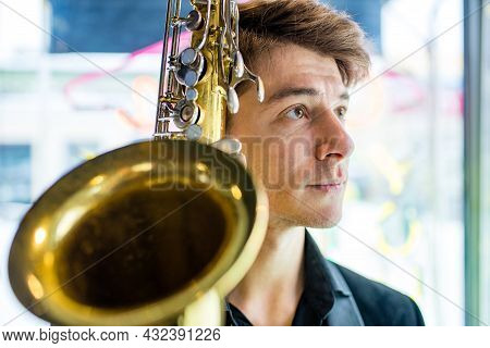 Saxophone In Hands Close-up Man In Black Outfit