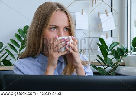 Young Woman Drinking Coffee Working On A Computer At Home, Calculating Monthly Exspences, Doing Home
