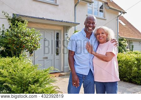 Portrait Of Smiling Senior Couple Standing Outside Home Together
