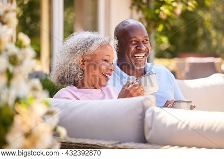 Retired Couple Sitting Outdoors At Home Having Morning Coffee Together
