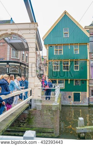 Alkmaar Netherlands - August 18 2012;tourists Crowd A Walkway Near A Canal-side Green And Yellow Bui