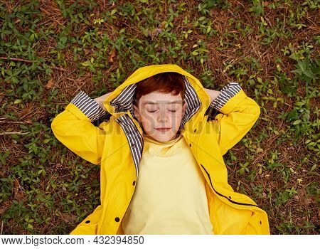 Top View Of Relaxed Dreamy Ginger Boy In Bright Yellow Raincoat With Hood Lying On Green Grass , Wit