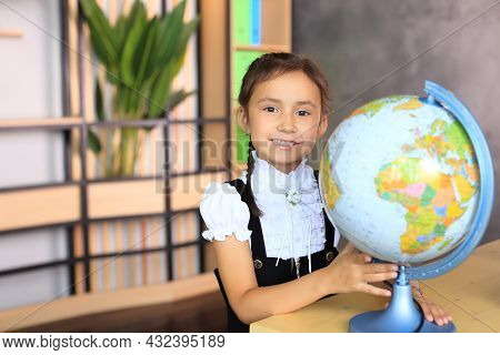 Portrait Of A Girl In A School Uniform With A Globe In Her Hands. Young Schoolgirl In The Class. The