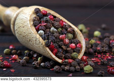 A Mixture Of Peppers In A Wooden Scoop Close-up. Pepper Mix. Traditional Spices.