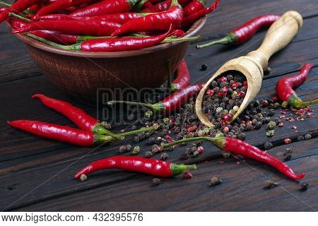 Red Hot Chili Peppers And A Mixture Of Peppers In A Wooden Spoon On A Wooden Table. Pepper Mixture.