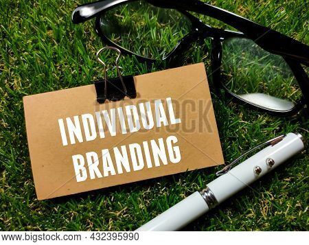Business Concept.text Individual Branding Writing On Brown Card With Glasses And Pen On Grass Backgr