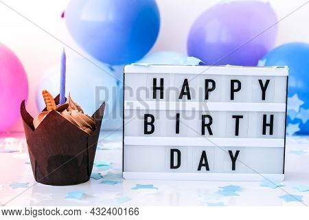 Lightbox With Text Happy Birthday And Chocolate Cupcake Candle On Abstract Defocused Blurred Festive