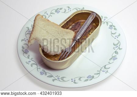 Canned Fish, Sardines In Oil, And Small Metal Fork With Three Prongs. Open Tin Can Without Lid And A
