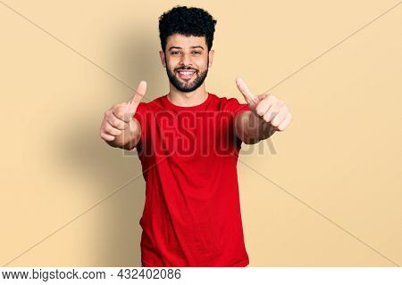 Young arab man with beard wearing casual red t shirt approving doing positive gesture with hand, thumbs up smiling and happy for success. winner gesture.
