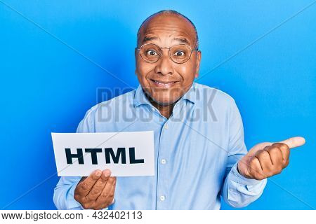 Middle age latin man holding html paper message screaming proud, celebrating victory and success very excited with raised arm