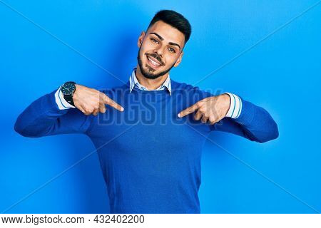 Young hispanic man with beard wearing casual blue sweater looking confident with smile on face, pointing oneself with fingers proud and happy.