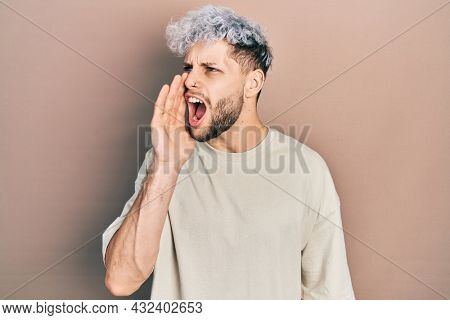 Young hispanic man with modern dyed hair wearing casual t shirt shouting and screaming loud to side with hand on mouth. communication concept.
