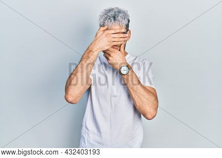 Young hispanic man with modern dyed hair wearing white t shirt and glasses covering eyes and mouth with hands, surprised and shocked. hiding emotion