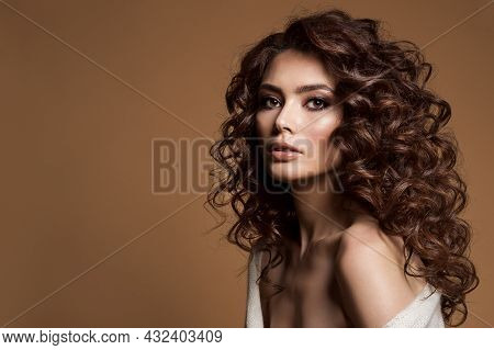 Curly Hair Woman. Beauty Hairstyle Girl Over Dark Brown Background. Brunette Model With Smokey Eyes