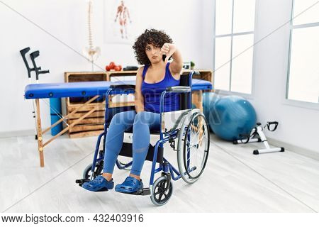 Young middle eastern woman sitting on wheelchair at physiotherapy clinic looking unhappy and angry showing rejection and negative with thumbs down gesture. bad expression.