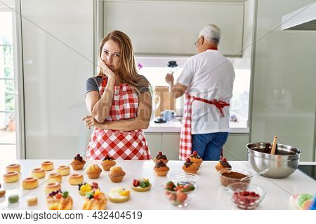 Middle age hispanic woman wearing apron cooking homemade pastries thinking looking tired and bored with depression problems with crossed arms.