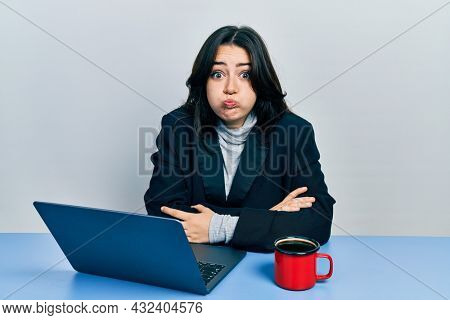 Beautiful hispanic business woman with arms crossed gesture at the office puffing cheeks with funny face. mouth inflated with air, catching air.