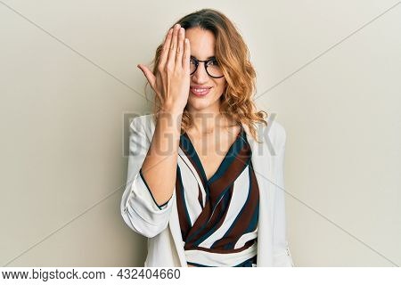 Young caucasian woman wearing business style and glasses covering one eye with hand, confident smile on face and surprise emotion.