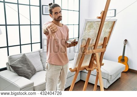 Young hispanic man with beard painting on canvas at home looking unhappy and angry showing rejection and negative with thumbs down gesture. bad expression.