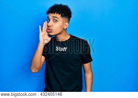 Young african american man wearing staff t shirt hand on mouth telling secret rumor, whispering malicious talk conversation