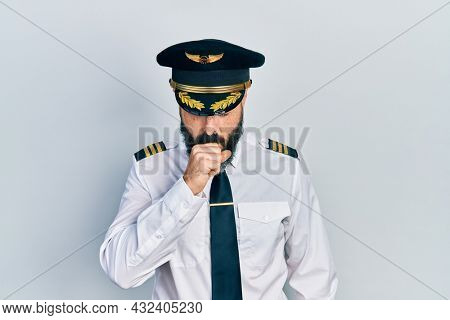 Young hispanic man wearing airplane pilot uniform feeling unwell and coughing as symptom for cold or bronchitis. health care concept.