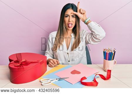 Young hispanic woman making valentine gift sitting on the table making fun of people with fingers on forehead doing loser gesture mocking and insulting.