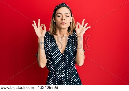 Young caucasian blonde woman wearing beautiful black and white dress relax and smiling with eyes closed doing meditation gesture with fingers. yoga concept.