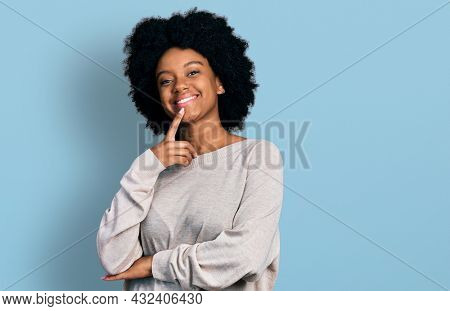 Young african american woman wearing casual clothes looking confident at the camera with smile with crossed arms and hand raised on chin. thinking positive.